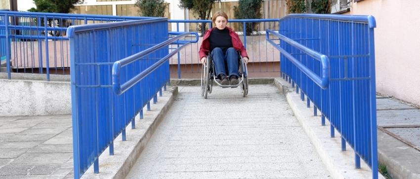 Fotografía de una mujer en silla de ruedas descendiendo por una rampa